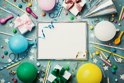 Party or birthday background. Silver frame with colorful balloon, gift box, carnival cap, confetti, candy and streamer on vintage blue table top view. Flat lay style. Holiday mockup.