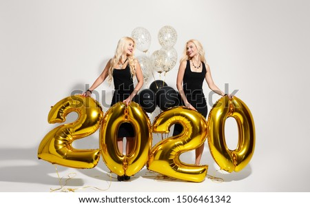 Party, people and new year holidays concept - tweens women in black dresses celebrating new years eve 2020. Golden air balloons isolated on white background.