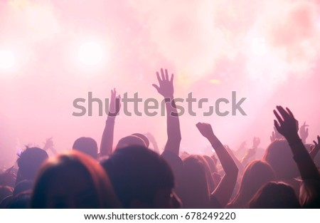 Party people  with crowd people hand up dancing in concert  club,  Silhouette hands of audience crowd people use smart phones enjoying the club party with concert. Blurry night club. #678249220