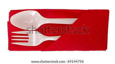 Party plastic spoon and fork on serviette, isolated