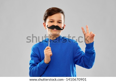 party props, photo booth and childhood concept - smiling boy in blue hoodie with black moustaches over grey background