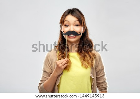 party props, photo booth and people concept - happy asian young woman with big black mustache over grey background