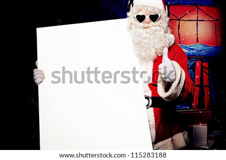 Party Santa Claus holding white board over Christmas background.