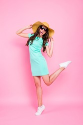 Party style concept. Vertical full length, legs, body, size portrait of girl in a teal dress and white sneakers holding her hat with her hands dancing and having fun isolated on shine pink background