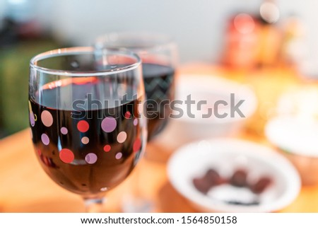 Party table setting with two glasses macro of red wine on table with blurry background of room and nobody in house #1564850158