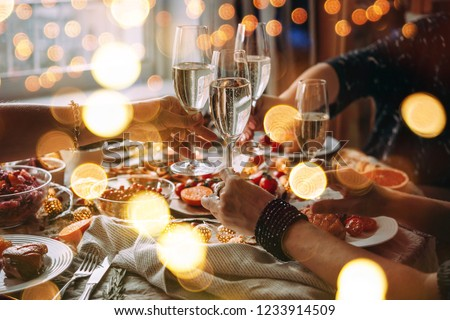 Party table with glasses of champagne. Friends celebrating Christmas or New Year eve. #1233914509