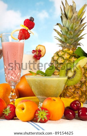Party table with summer fruits and colorful smoothies