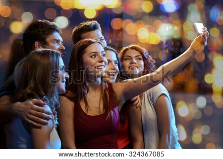 party, technology, nightlife and people concept - smiling friends with smartphone taking selfie in club #324367085