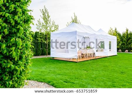 Party tent - white garden party or wedding entertainment tent in modern garden #653751859