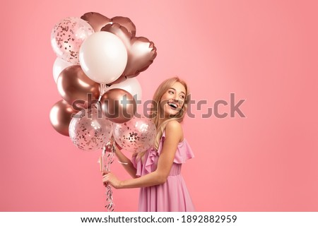 Party time. Charming blonde woman in stylish dress holding bunch of birthday balloons over pink studio background, copy space. Joyful young lady having fun celebration, enjoying holiday