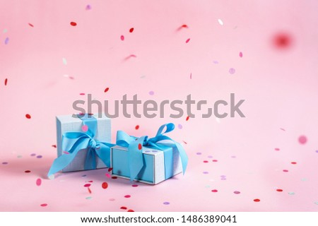 Party time concept! Two beautiful and blue wrapped present or gift box with ribbon isolated against shine pink background with copy or empty space for text with paper and colorful confetti decorations
