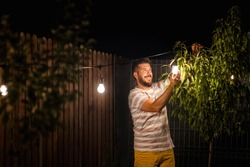 Party time in backyard with happy man hanging string lights in trees – Weekend night mood with smiling millennial guy arranging the light garland for outdoor dinner party in garden