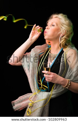Partying woman with a alcoholic beverage blowing a streamer