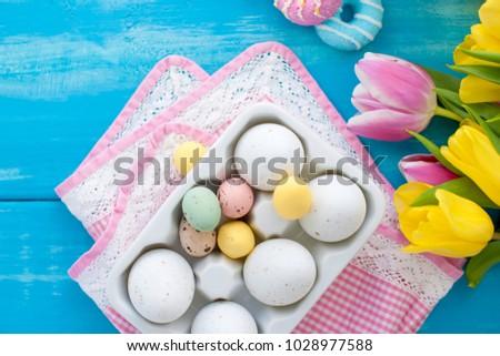 Pasen gekleurde eieren. Een boeket van verse lente tulpen. Blauwe achtergrond Sweets. Briefkaart, vrije ruimte voor tekst. Stockfoto ©