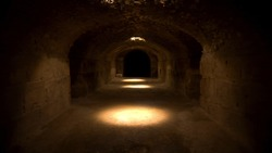 Pass through a long and dark Roman basement. Basement under the amphitheater in El Jem, Tunis. Ancient roman building. The camera is approaching