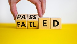 Passed or failed symbol. Businessman turns wooden cubes and changes the word 'failed' to 'passed' on a beautiful yellow table, white background. Business and passed or failed concept. Copy space.