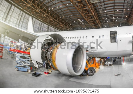 Passenger aircraft on maintenance of engine and fuselage repair in airport hangar. View airplane engine