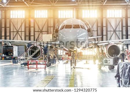 Passenger aircraft on maintenance of engine repair in airport hangar
