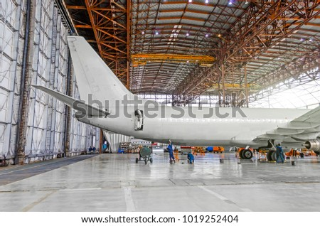 Passenger aircraft on maintenance of repair, a view of the tail and the rear of the fuselage in airport hangar