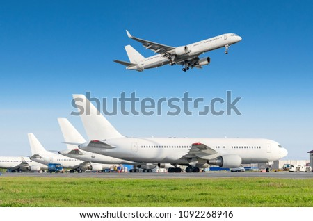 Passenger aircraft row, airplane parked on service before departure at the airport, other plane push back tow. Airplane landing to the runway in the blue sky