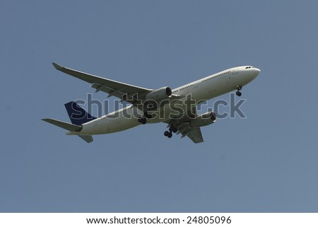 Passenger airliner during landing approach against blue sky