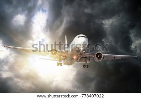 Passenger airplane departs from the dark storm clouds in bad weather on landing in the air