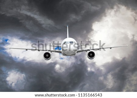 Passenger airplane flies through the turbulence zone through the lightning of storm clouds in bad weather