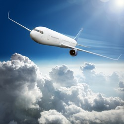 Passenger airplane flying above dramatic clouds concept for travel and vacations