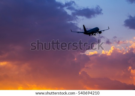 Passenger airplane flying in the sky at sunset