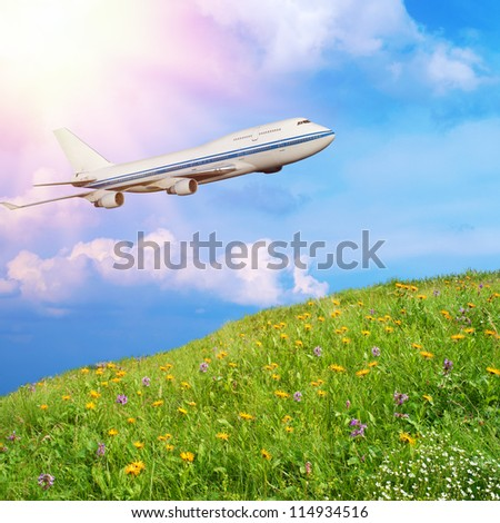 passenger airplane in the clouds against the backdrop of mountain meadow with grass and flowers. travel by air transport. flying to the top of the airliner. nobody