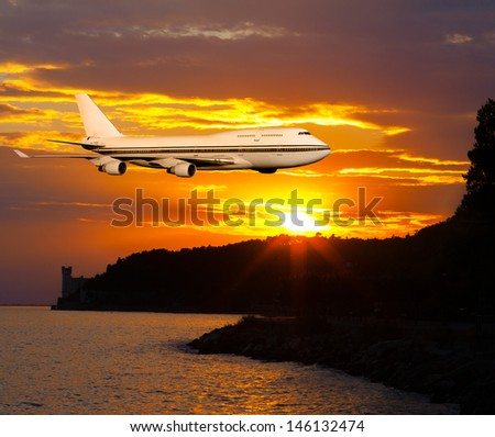 passenger airplane in the clouds at sunset or dawn. Tourist Card. plane on a background of sea and mountains. travel by air transport. flying to the top of the airliner. nobody