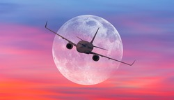 Passenger airplane in the sky against super moon at sunset