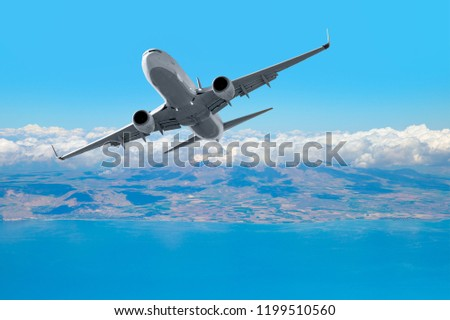 Passenger Airplane is flying in blue cloudy sky over the sea.