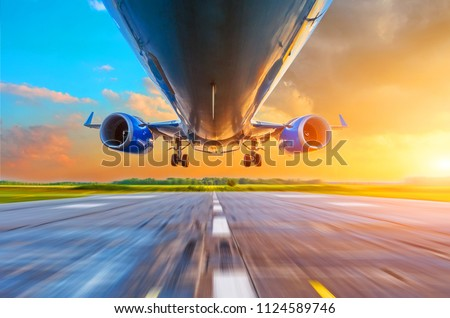 Passenger airplane landing at sunset on a runway. View of engines, fuselage, chassis