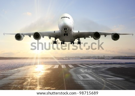 Passenger airplane landing on runway in airport. Evening