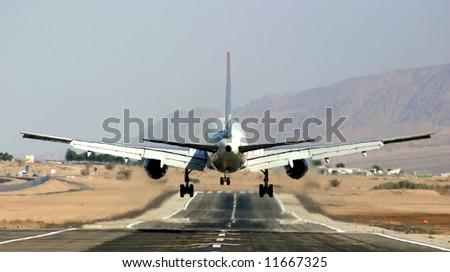 Passenger airplane landing on runway in airport of Eilat, Israel.