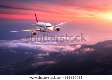 Photo of  Passenger airplane. Landscape with big white airplane is flying in the red sky over the clouds and sea at colorful sunset. Passenger aircraft is landing at dusk. Business trip. Commercial plane.Travel