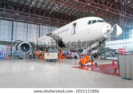 Passenger airplane on maintenance of engine and fuselage repair in airport hangar. Aircraft with open hood on the nose and engines, as well as the luggage compartment.