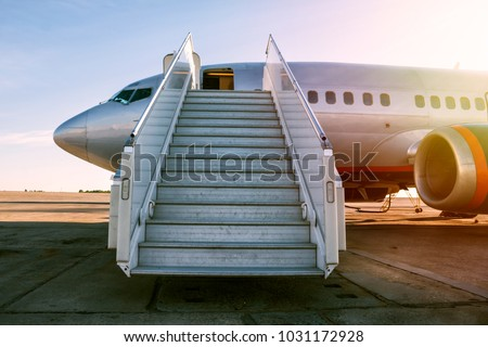 Passenger airplane with a boarding steps in the morning sun