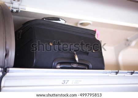 Passenger baggage stow in the cabin overhead bin in the commercial airplane, selective focus. #499795813