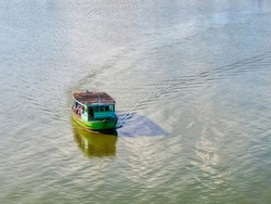 Passenger boats run across the river in the middle of the Tha Chin River.