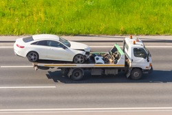 Passenger car with broken front bumper and hood in an accident loaded onto an evacuation truck rides, aerial view from above