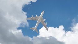 Passenger commercial airplane flying above head as shot from the ground in deep blue cloudy sky
