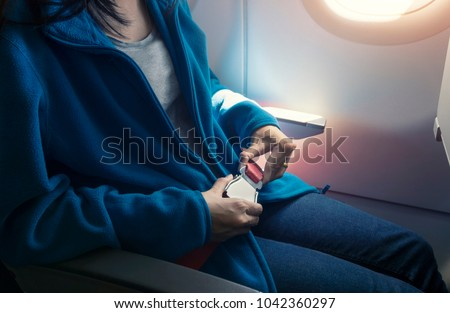 Passenger fastening seat belt while sitting on the airplane for safe flight. Safety travel.