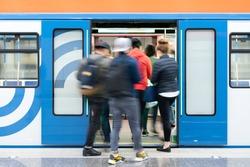 Passenger flow concept. People go on subway train. Passengers are blurred, movement is shown. Train station.