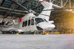 Passenger helicopter and airplanes in the hangar. Rotorcraft and aircrafts under maintenance. Checking mechanical systems for flight operations