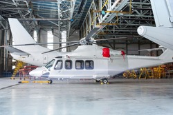 Passenger helicopter and airplanes under maintenance. Checking mechanical systems for flight operations. Rotorcraft and aircrafts in the hangar