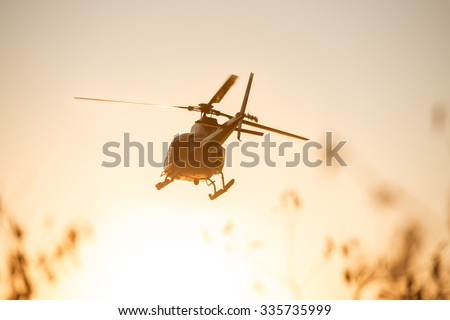 Passenger Helicopter flying in sunset sky