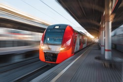 Passenger high speed red train with motion blur in station platform with benches for people