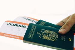 passenger holding uae passports and airline tickets in airport - departures pass gate